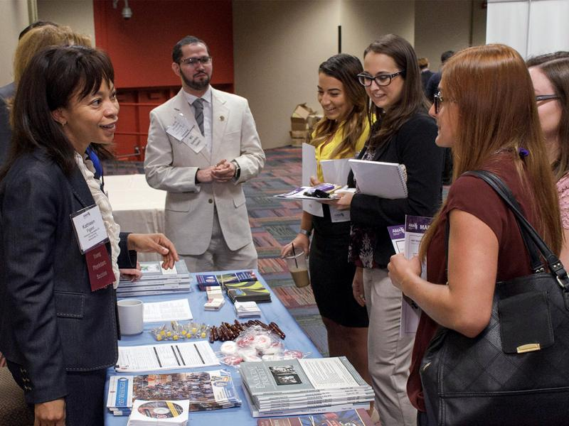 A group of medical students gather at an MSS table at the Annual Meeting.