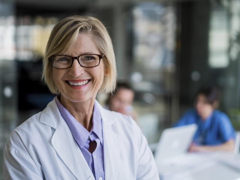 Portrait of a smiling female physician in a classroom setting.