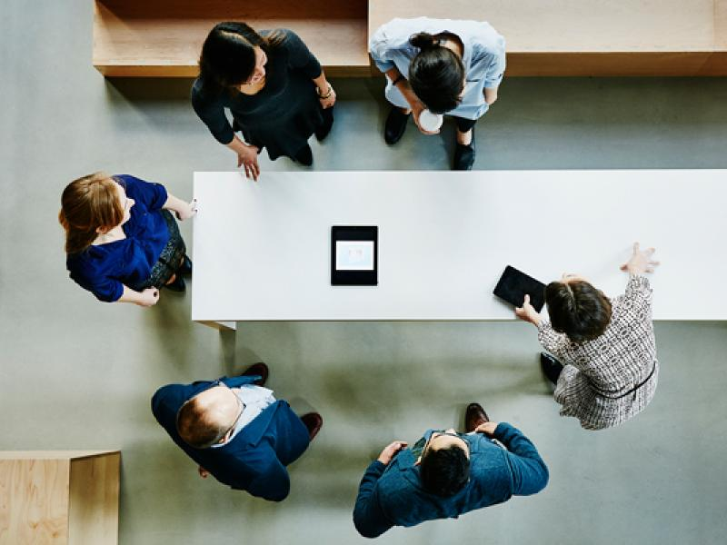 A top view looking down on six people standing around a table that holds a small computer pad.