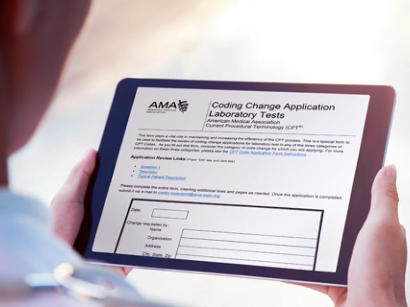A physician holds a tablet, which displays the AMA Coding Change Application.