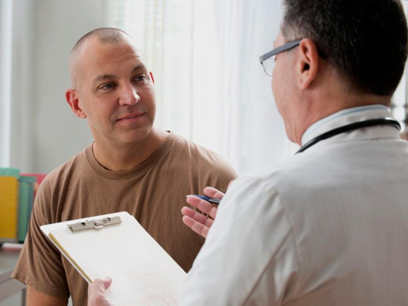 A middle-aged physician speaks to a U.S. Army officer in a doctor's office.
