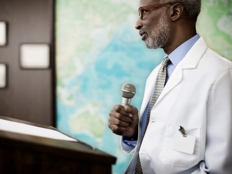 A gray-haired physician leads a seminar to teach other physicians how to be leaders as the health care system changes.