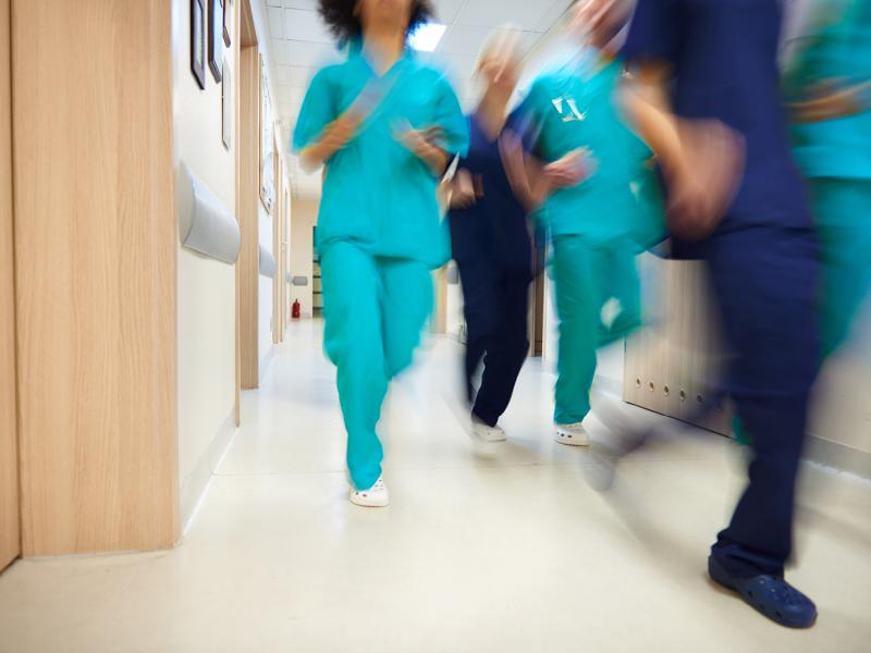Physicians running down a corridor.