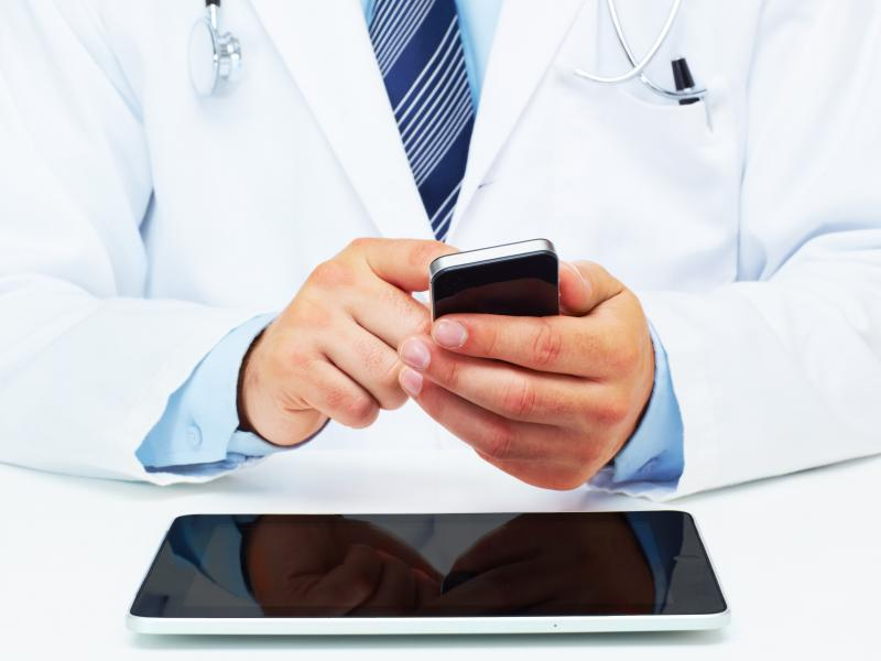 Physician holding a cell phone.