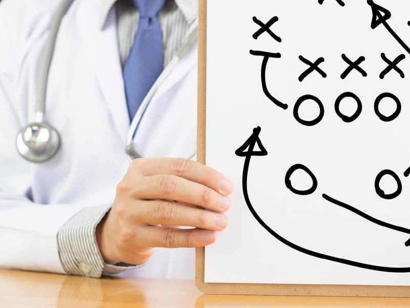 A close-up photo of a physician's hands holding a clipboard that displays a game strategy.