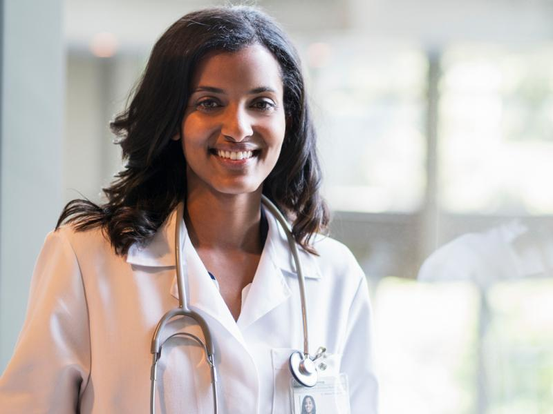 A young physician in a white coat with a stethoscope around her neck smiles and looks at the camera.