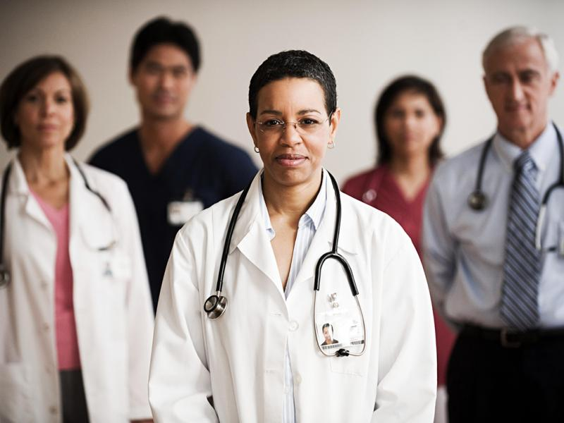 A female physician in a white coat with a stethoscope around her neck faces the camera, with 4 other physicians and medical personnel behind her.