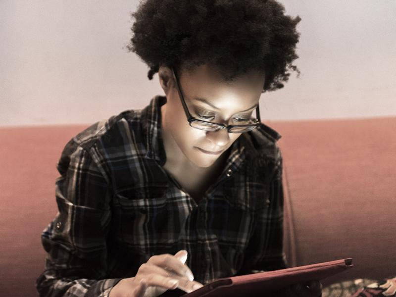 A resident in a dimly lit room looks at her tablet.