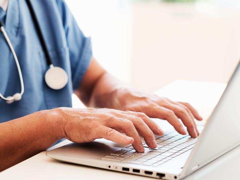 Physician entering data into a laptop.