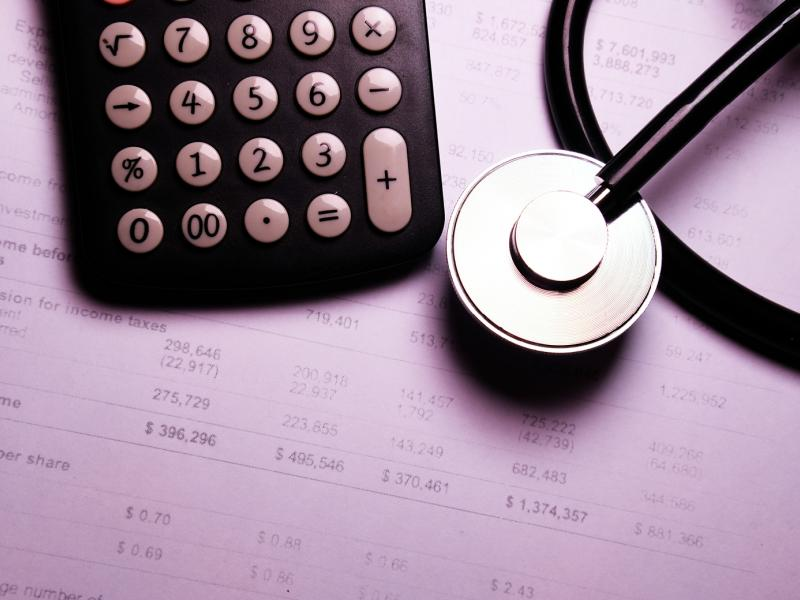 A stethoscope and calculator sit on top of a medical billing statement.