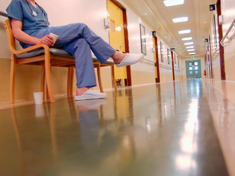 A female doctor sitting on a chair in an empty hospital hall with two empty cups of coffee.