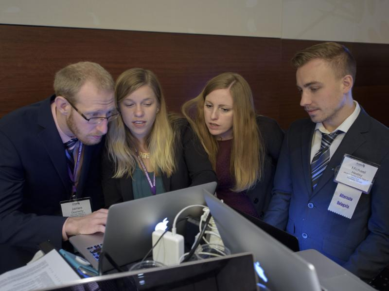 A group of AMA delegates review something in front of a laptop.