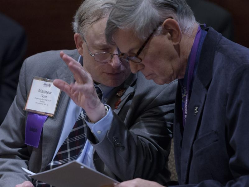 Two AMA delegates discuss an issue at a meeting.