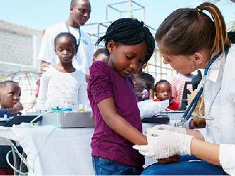 Medical student providing care to young girl at community event