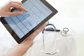 Person holding tablet that shows waves on the screen, next to white coat and stethoscope