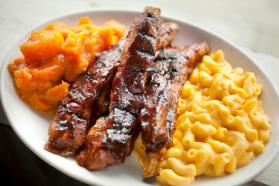 Plate heaping with bbq ribs, macaroni and cheese