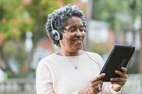 Woman in headphones looking at computer tablet