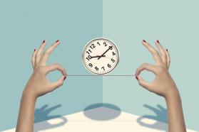Two hands balancing a clock
