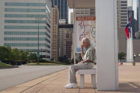 Older man waiting at a bus stop