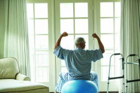 Patient sitting on an exercise ball next to a walker