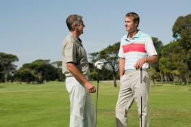 Two men talking on a golf course