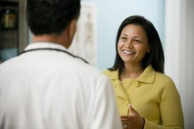 A smiling patient speaking to a physician