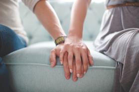 Tight shot of couple sitting on sofa holding hands