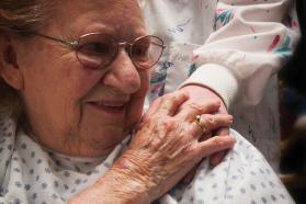 Elderly woman patient smiling and holding hand of caregiver