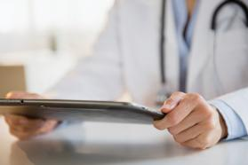 Close up of physician holding a tablet in his hands
