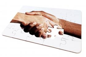 Puzzle of two hands shaking with one puzzle piece missing