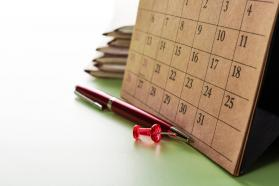 Paper calendar with a red pen and red thumbtack in front of it