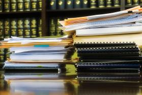 Stack of papers and folders on desk with law books in background.