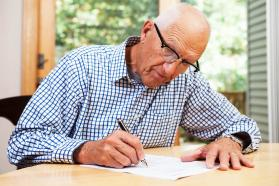 Elderly man writing
