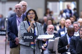 Female delegate speaking into microphone at the 2019 HOD Interim Meeting.