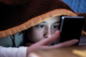 Child looking at mobile phone underneath a blanket