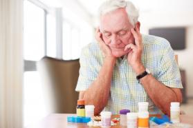 Elderly man looking at prescription bottles