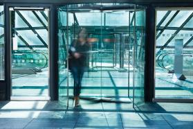 Figure walking through revolving door