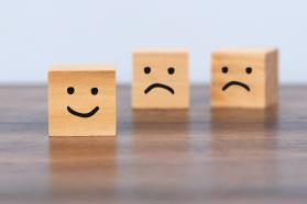 Three wooden blocks with drawn happy and sad faces