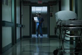 Physician standing in hospital hallway, looking at a chart