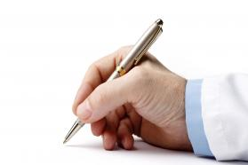 Close-up of a man signing with a pen