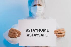 "Health care professional holding a ""Stay home, Stay safe"" sign"
