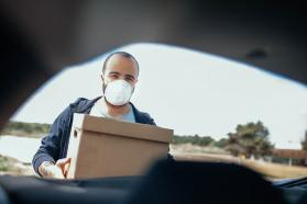 Person wearing facemask and holding a box