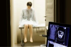 Patient in hospital gown getting a scan.
