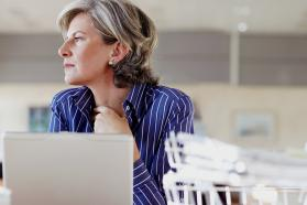 Middle-aged woman sitting in front of laptop.