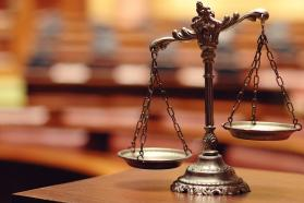 Unbalanced scales of justice on table top.