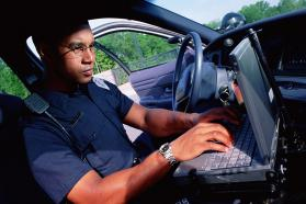 Police officer using laptop in his vehicle.