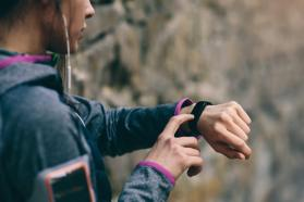 A female runner checks her fitness tracker to see how her workout is going.
