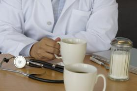 A doctor sharing coffee and a chat with a colleague on a break at their office.