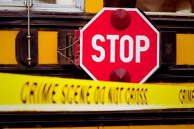 Crime scene tape pulled in front of a school bus with the stop sign arm extended