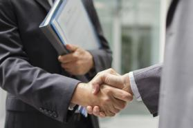 Two businessmen shaking hands outside of a building